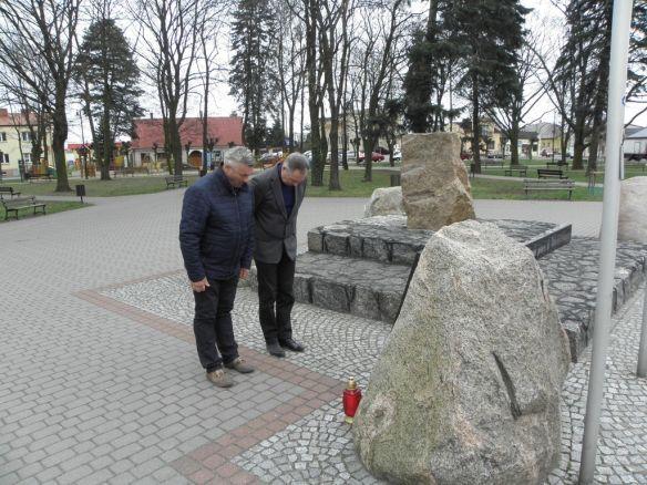 Wójt i Przewodniczący Rady Gminy Babiak stoją przed pomnikiem ofiar zbrodni katyńskiej.
