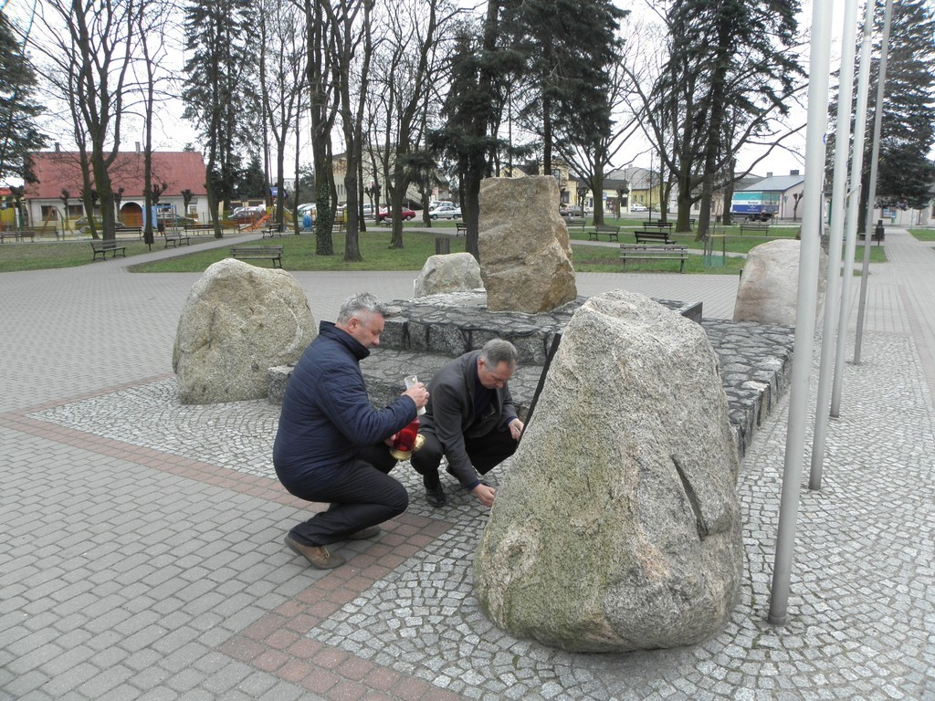 Wójt i Przewodniczący Rady Gminy Babiak zapalają znicze pod pomnikiem ofiar zbrodni katyńskiej