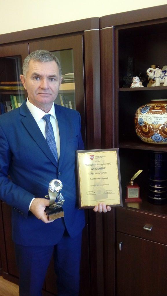 dr Marek Tomicki, dyrektor Szkoły Podstawowej w Bogusławicach wraz z dyplomem i statuetką.